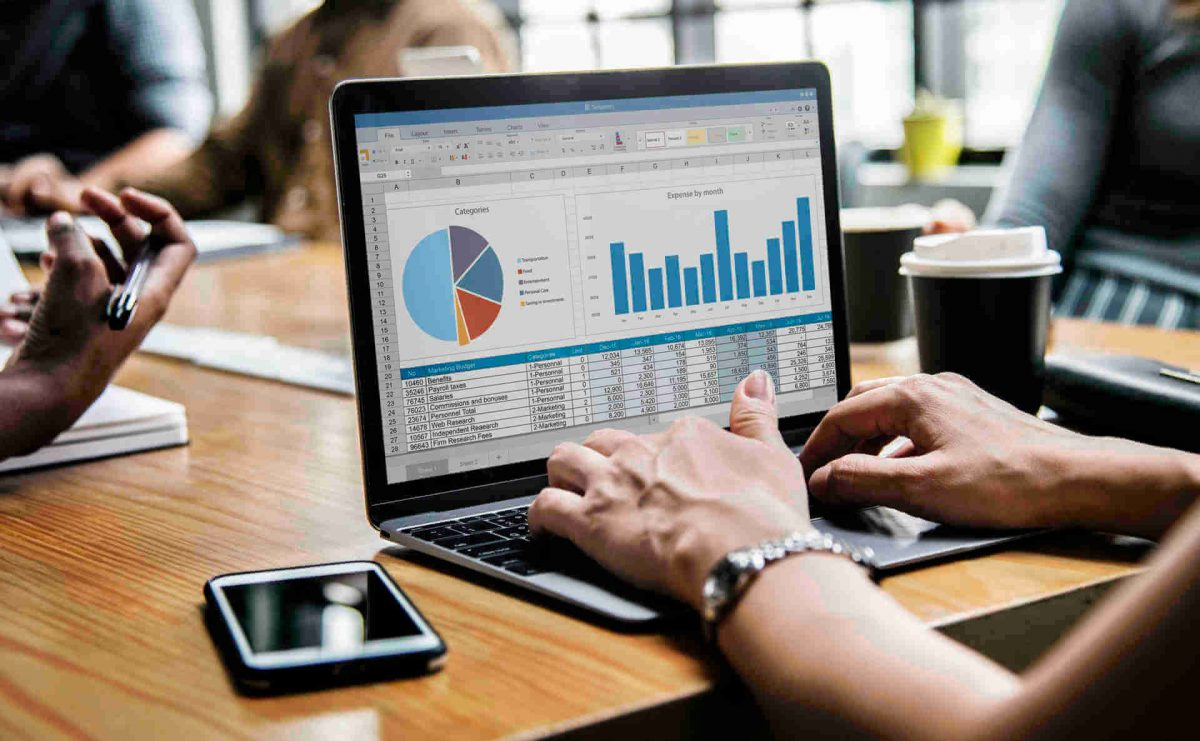 Mesa de reunião com um laptop aberto com gráficos de análise de dados na tela.